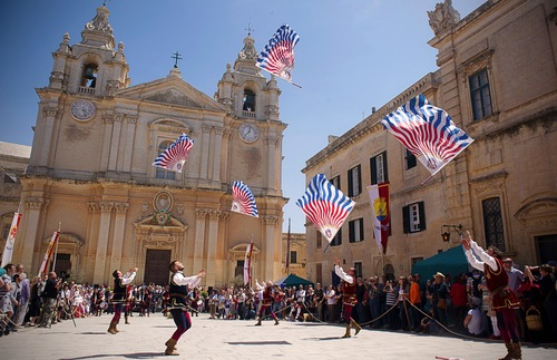 Men perform a flag dance at a medieval-style festival in Mdina, Malta