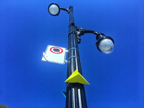 A yellow marker on a street lamp in Montreal
