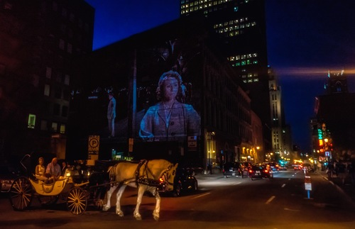 A horse and carriage pass a personal sound-and-light show happening on the streets of Old Montreal.