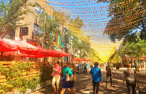 People stroll along St. Catharine Street, which is overhung by a canopy of colorful balls