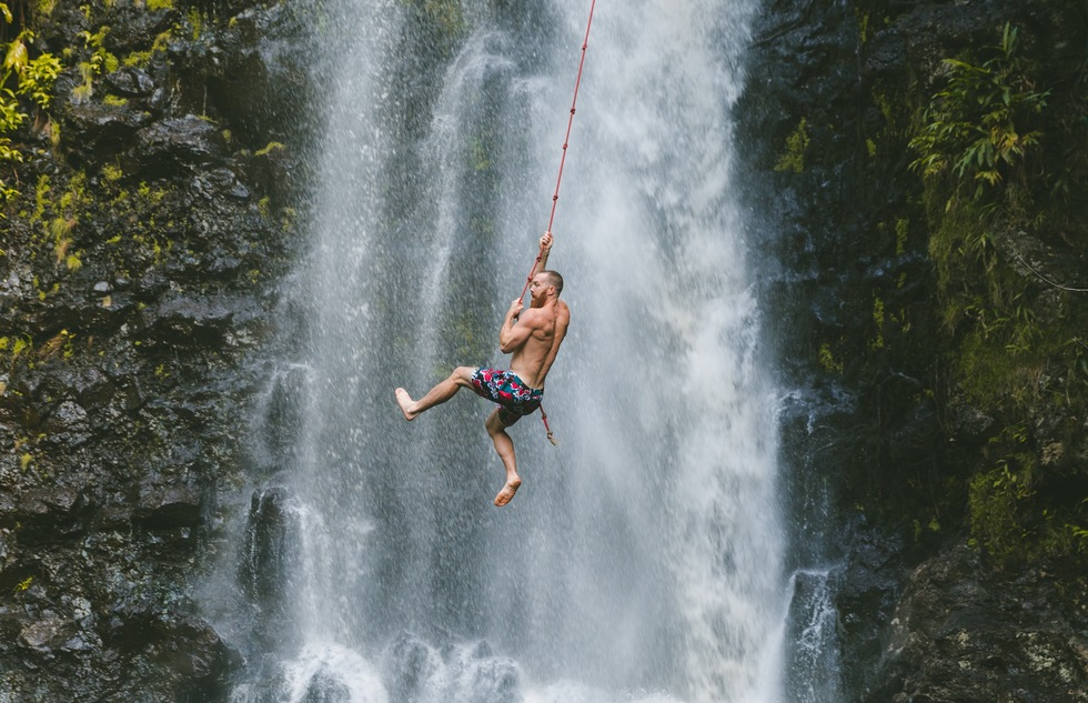 Waterfall rope swinging in Kauai, Hawaii