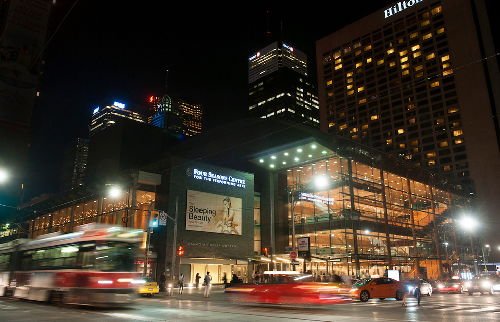 An exterior night shot of the Four Seasons Centre for the Performing Arts, with taxis and streetcars outside