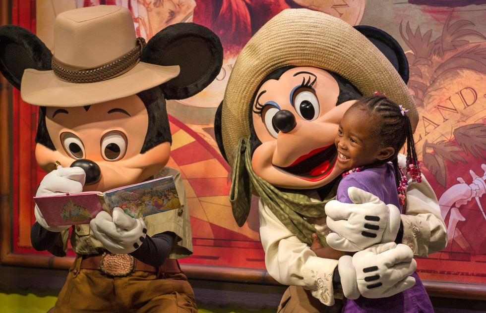 Mickey and Minnie Mouse greet a child at Walt Disney World in Florida.