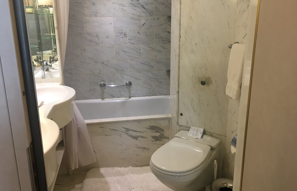 One small bathroom is set next to the entry door of each suite. It is clad in marble and features a double sink and a shower (but no bathtub).