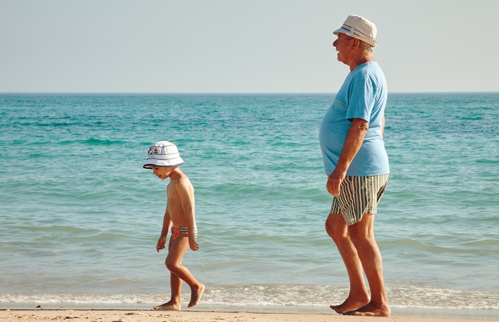 A man and boy walk on the beach.