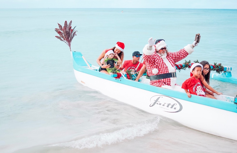 Santa arriving by outrigger canoe at Outrigger Waikiki Beach Resort in Honolulu