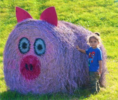 A girl with a decorated hay bale at Heaven Hill Farm