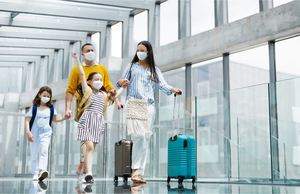A masked family having fun in an airport