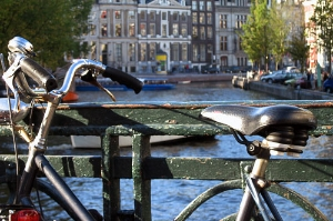 a bike sits on a bridge overlooking the Amsterdam canals