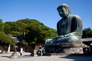 Praying before Daibutsu (Big Buddha) statue at Kotokuin Temple in Kamakura, Japan.