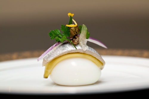 Gribiche: soft boiled quail egg garnished with flavor of sauce gribiche, a slice of cornichon, white anchovy filet, julienne red onion, fried caper, lemon segment, lemon zest, parsley at Next Restaurant. Photo: Christian Seel