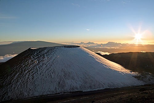 A mecca for skiiers and snowboarders, Mauna Kea towers above the clouds at sunset.