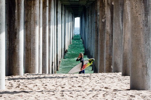 Surfer under a pier at Huntington Beach, California.