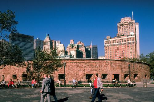 People crossing an open area in Battery Park, with the red sandstone ring of Castle Clinton and towering buildings set against a blue sky behind it.