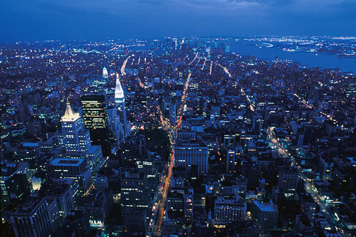 A view of New York City from the Empire State Building, lights twinkling from the street lights and the windows in the skyscrapers and city buildings at night.