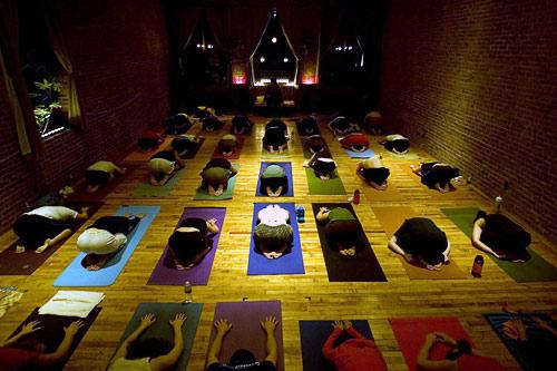 Candlelight yoga in the classic exposed-brick studio of Yoga to the People. Courtesy Connie Aramaka