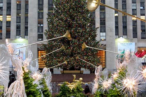 A row of illuminated angels before the famous tree in Rockefeller Plaza, New York City.
