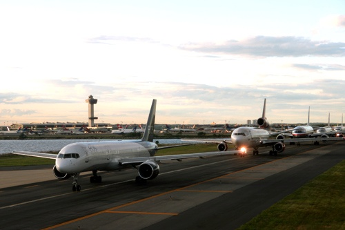 A long line of planes queued on the tarmac, awaiting takeoff at JFK International Airport.