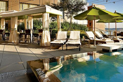 Poolside cabanas and lounge chairs dot the rooftop pool at the Four Seasons Hotel Seattle.