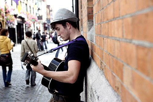 A street musician strums for tourists strolling Temple Bar's lively cobblestone streets.