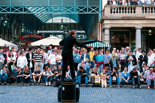 A street performer in Covent Garden being watched by a crowd of people.