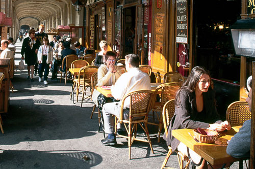 Tourists and Parisians alike enjoy refreshments beneath the arcaded cafes and bars of the Place des Vosges.