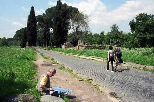 Travelers stroll or take a break on the pastoral Appian Way.