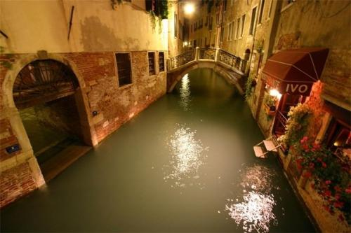 view of a narrow canal at night time in Venice