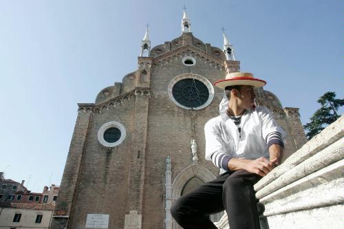 A gondolier sits down in front of the Basilica Santa Maria Gloriosa dei Frari, Venice.