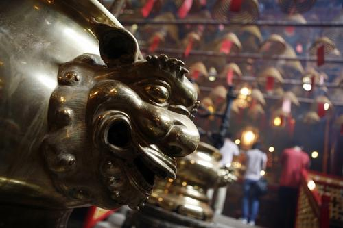 A brass lion guards an altar at Man Mo Temple.