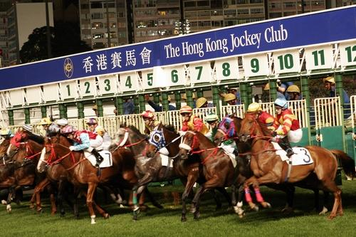Horses come out of the gate at Happy Valley Racecourse, where both locals and visitors put money on the races.
