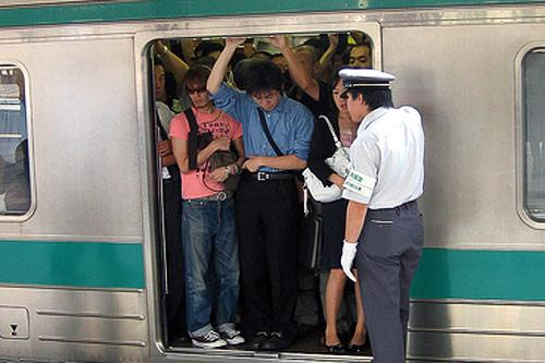 White-gloved attendants often help passengers board crowded subway trains in Tokyo.
