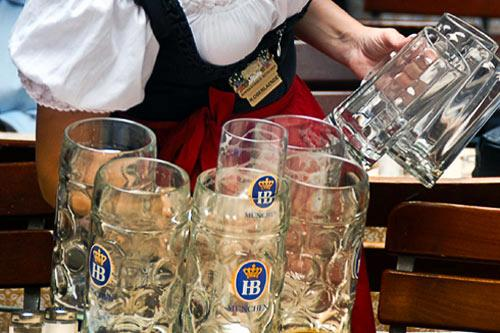 A waitress wearing traditional Bavarian garb cleans up empty beer steins.