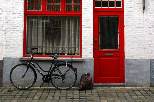 A bicycle leaning against a house in Bruges, Belgium.