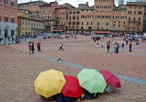 The most beautiful piazza in Italy is dramatically shaped like a sloping scallop shell or fan, divided into nine sections in honor of the Council of Nine, who ruled Siena during its golden age, and graced with a copy of the original Fonte Gaia (Fountain of Joy), created by the city's own Jacopo della Quercia.<br><br><em>Photo Caption: The Campo in Siena, Italy on a drizzly March morning.</em>
