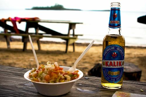 Fresh conch salad and cold Kalik beer at Governor's Harbour Friday Night Fish Fry, Bahamas.