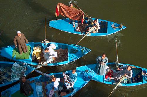 Vendors sell their wares to tourists, who are aboard a cruise ship going through a set of locks on the Nile River.