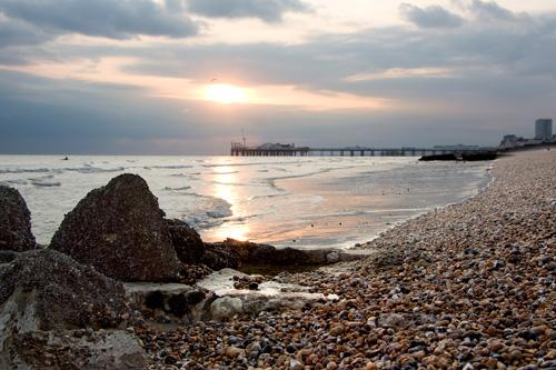 Brighton's pebble beach at dusk Palace Pier in the background and mussel bank in the foreground