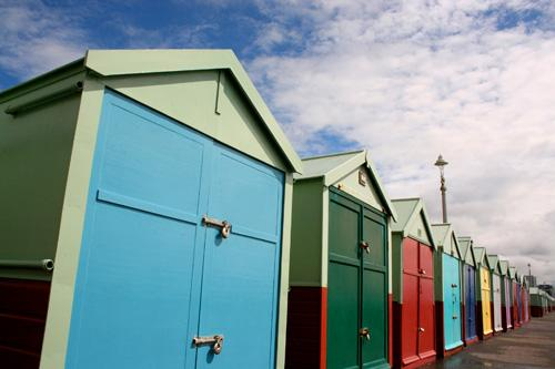 Brightly coloured beach huts in a row on Brighton seafront, England
