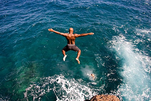 Daring divers leap off the craggy rocks at Hulopoe Bay, where crystal clear water also attracts snorkelers and swimmers.
