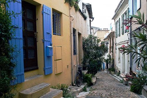 A colorful building and view of a narrow street in Arles
