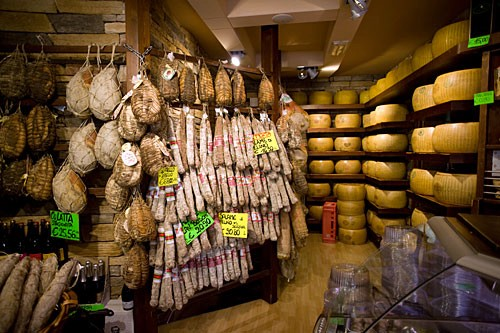 Enjoy the local specialities--here, Parma's hams and cheeses.