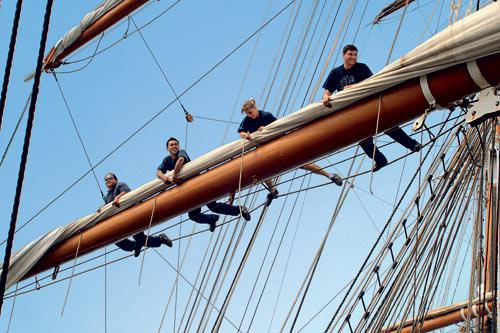 Crew members secure the sails aboard Sea Cloud II.