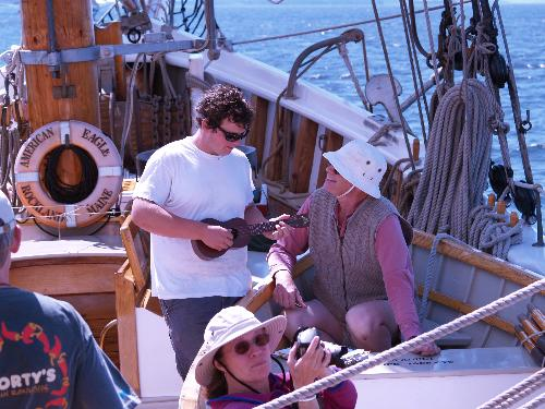 A crewmember and a passenger compare ukulele chords aboard American Eagle.