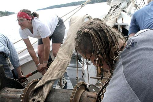 Deck hands aboard Timberwind raising the anchor by hand.