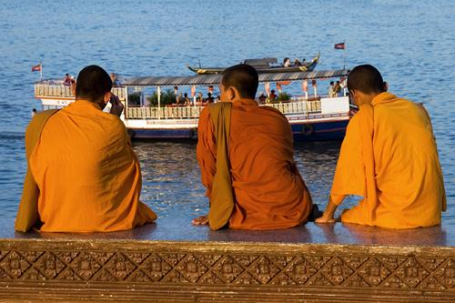 Buddhist monks in traditional orange robes, sitting along the riverfront in Phnom Penh