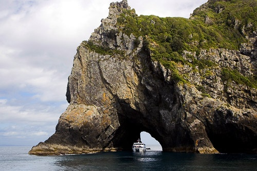 Boat passing through Hole in the Rock in New Zealand's Bay of Islands.