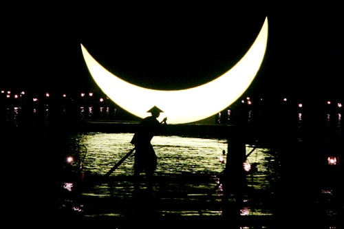 A cormorant fisherman rows his bamboo boat against the backdrop of a giant moon on the Li River,