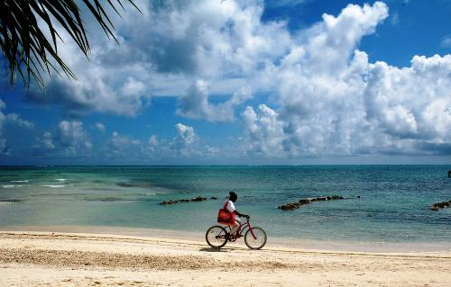 A woman rides her bike along the beach of San Pedro on Ambergris Caye