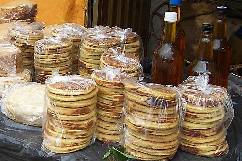 A variety of arepas being sold in stacks by a street vendor.